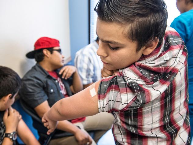 Abraham Vidaurre, 12, checks his arm after receiving an HPV vaccination at Amistad Community Health Center in Corpus Christi, Texas, in 2016. Though gender differences in vaccine rates have narrowed, more girls than boys tend to get immunized against HPV