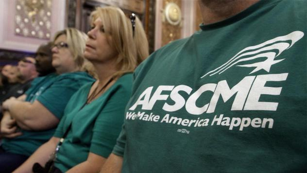Members of the American Federation of State County and Municipal Employees union, or AFSCME, listen to a council executive speak about conditions at state prisons and detention centers in Illinois.