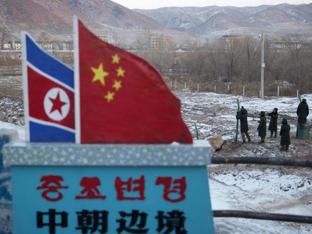 """A concrete marker with the North Korean and Chinese national flags has the words """"China North Korea Border,"""" at a crossing in the Chinese border town of Tumen in eastern China's Jilin province."""