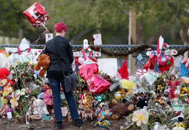A Marjory Stoneman Douglas High School student stops to look at one of the memorials following their return to school in Parkland, Fla., on Feb. 28. Wednesday, the Senate Judiciary Committee is holding a hearing on school safety.