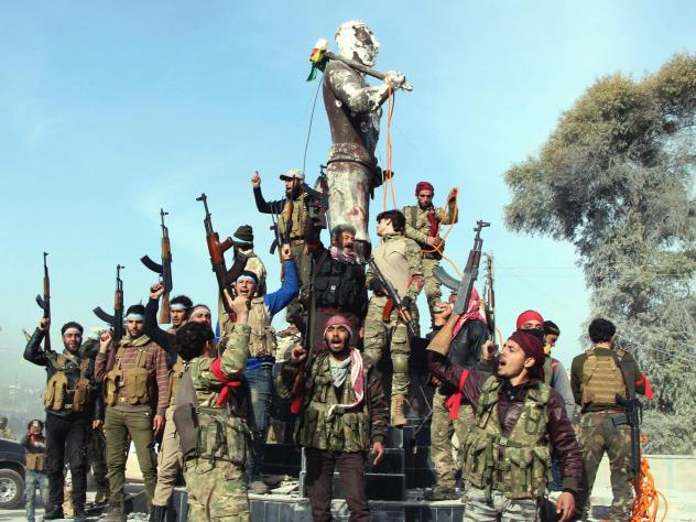 Turkey-backed Free Syrian Army soldiers celebrate around a statue of Kawa, a mythology figure in Kurdish culture as they prepare to destroy it in city center of Afrin, northwestern Syria, early Sunday.