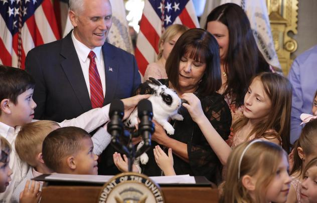 """Vice President Pence and his wife Karen Pence let children pet their family rabbit """"Marlon Bundo"""" during an event with military families in the Eisenhower Executive Office Building in May 2017."""