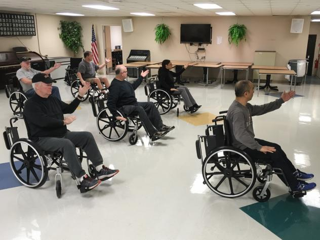 Medical anthropologist Zibin Guo (center) adapted tai chi for people with limited mobility. Though there's little research evidence confirming that tai chi eases drug cravings or symptoms of post-traumatic stress, the veterans in Guo's class say the prog