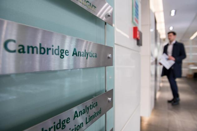 Signs for Cambridge Analytica in the lobby of the company's headquarters on March 21, 2018 in London. Some of the company's claims about its role in President Trump's 2016 campaign suggest it may have violated U.S. campaign finance laws.