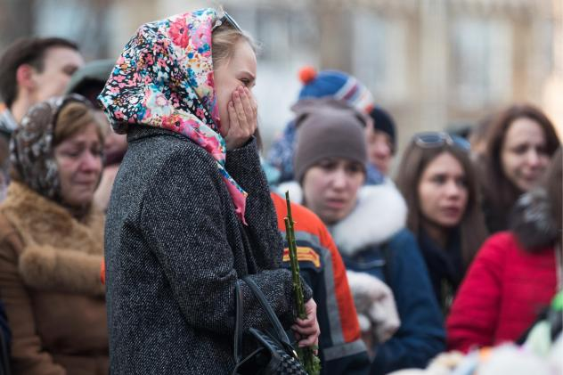 """People lay flowers at a makeshift memorial in tribute to the victims of a fire at a shopping centre in Kemerovo, Russia on Tuesday. Russian authorities denounced what they called """"flagrant violations"""" of safety norms that led to the deaths of 64 people,"""