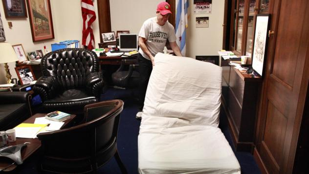 Rep. Mike Quigley, whose Washington, D.C. office doubles as his home away from Chicago, lays his mattress onto the floor before going to sleep in 2010.