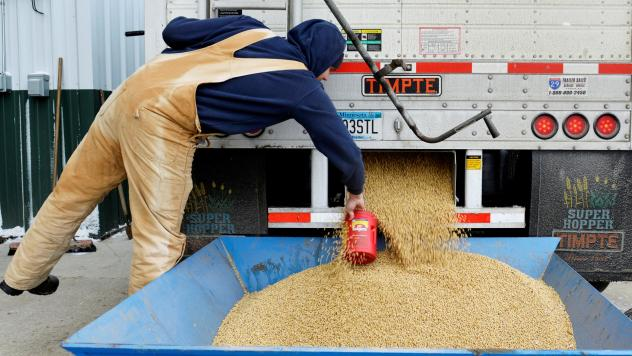 China currently buys nearly a third of the U.S. soybean crop — but the country plans to impose tariffs, in response to a Trump administration plan. Here, a worker takes a sample from a truckload of soybeans in Fargo, N.D., last December.