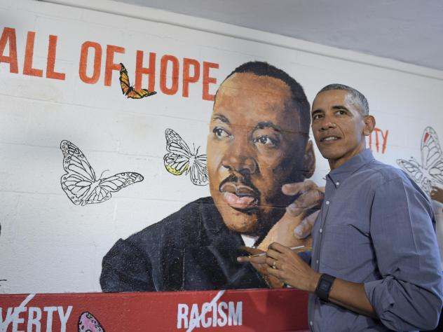 Then-President Barack Obama helps paint a mural of Martin Luther King Jr. in 2017.