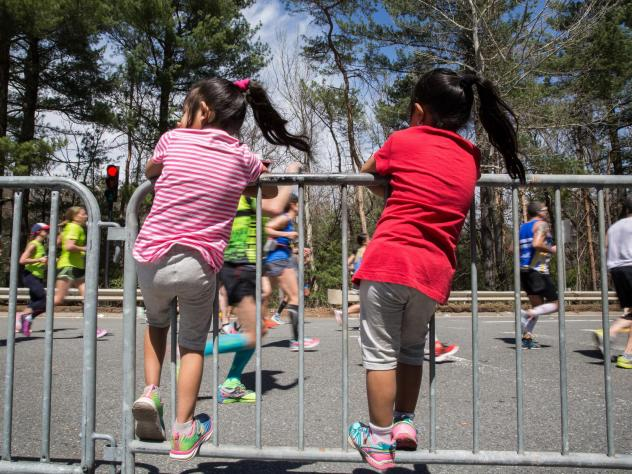 """Children climb the barrier to watch the Boston Marathon runners in the iconic """"scream tunnel"""" near Wellesley College on April 17, 2017, in Wellesley, Ma."""