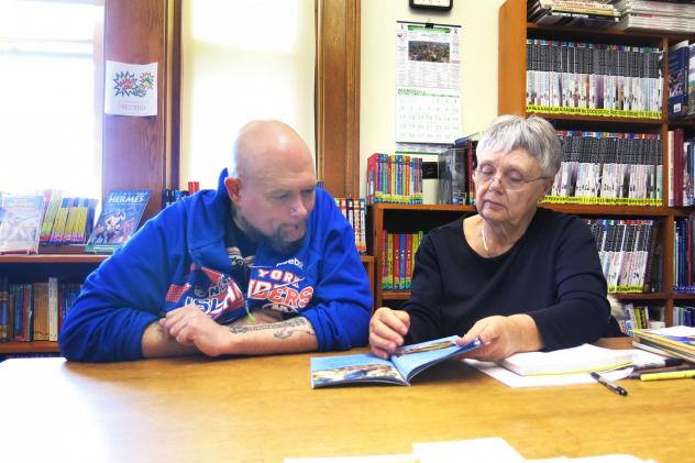 """Cindy Duell keeps a shelf of """"wish books"""" that she hopes to be able to read one day."""