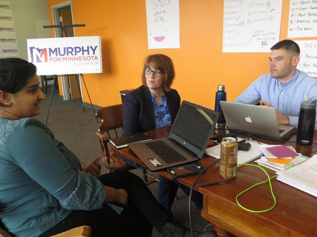 Campaign staff member Aisha Chughtai (left) speaks with Erin Murphy (center), a Democratic candidate for Minnesota governor, at the campaign's St. Paul headquarters as colleague Charles Cox looks on. Chughtai and Cox are members of a newly formed campaig