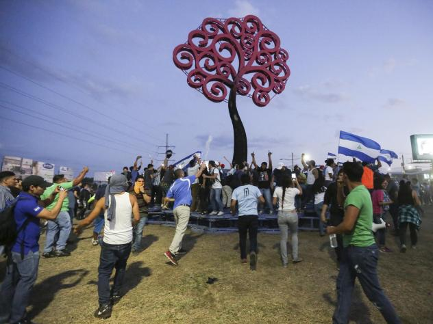 Men cut cables and metal parts to sell on the market from the Nicaraguan Government steel tree (Life Trees) burnt down during a protest against the government's reforms in the Institute of Social Security (INSS), in Managua on Sunday.