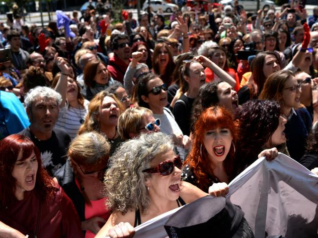 """Protesters gather outside the High Court of Navarra Thursday behind a banner reading """"I Believe You"""" while awaiting a verdict on five men accused of the multiple rape of a woman during Pamplona's San Fermin festival in 2016."""