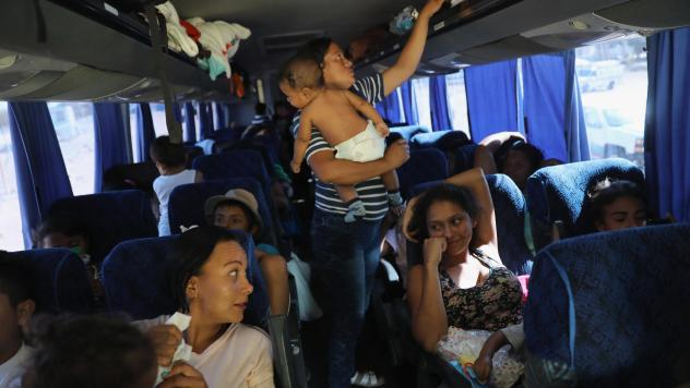 Central American asylum-seekers ride a bus to Tijuana on Wednesday, while passing through San Luis Rio Colorado along the U.S.-Mexico border. Hundreds of immigrants, the remnants of a caravan of Central Americans that began almost a month ago, set out on
