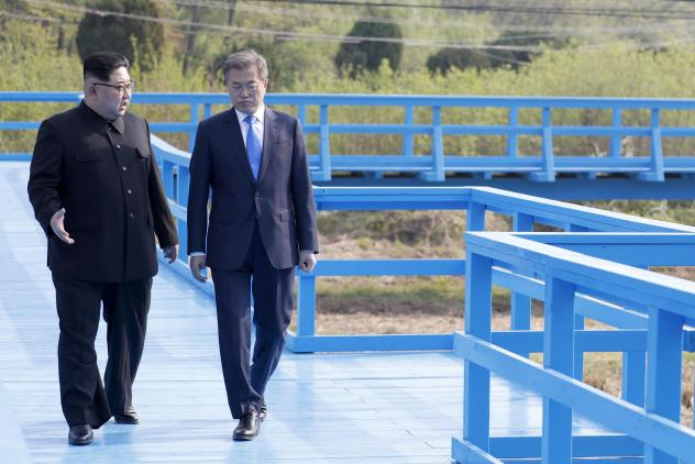 North Korea's leader Kim Jong Un (left) and South Korea's President Moon Jae-in walk on a bridge at the truce village of Panmunjom Friday. South Korea says Kim told Moon of the plan to shut the test site.