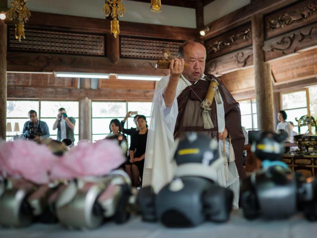 A girl wraps a Sony's pet robot AIBO after a robots' funeral at the Kofukuji temple.