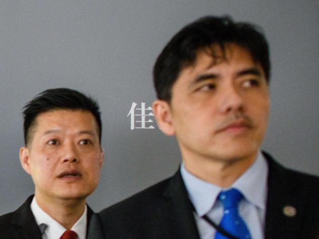 """This 2017 photo shows the man on the right, identified by local Hong Kong media as former CIA agent Jerry Chun Shing Lee, standing in front of a member of security at the unveiling of Leonardo da Vinci's """"Salvator Mundi"""" painting at the Christie's showro"""