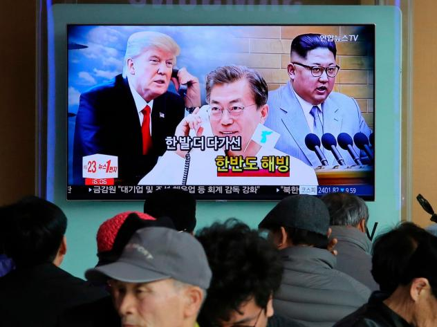 """People watch a TV showing images of North Korean leader Kim Jong Un (right), South Korean President Moon Jae-in and U.S. President Donald Trump — and the words """"Thawing Korean Peninsula"""" — at a railway station in Seoul, South Korea on March 7."""