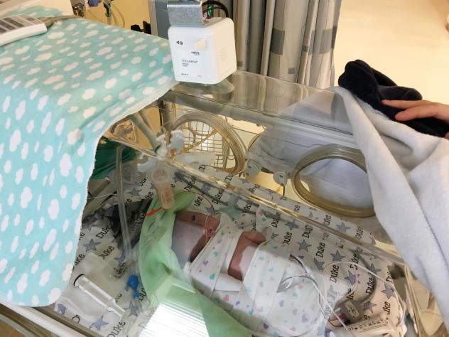 Jill Brothers, with baby Duke, one of her twins born at 27 weeks. She visited them every day during their NICU stay, and watched them online from home.