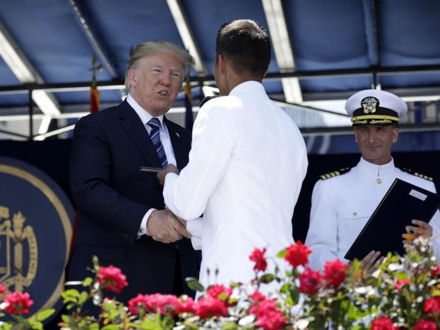 President Trump congratulates a U.S. Naval Academy midshipman Friday in Annapolis, Md.