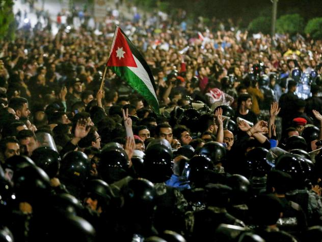 Protesters demonstrate outside the prime minister's office in Amman late on June 2, as security forces stand on alert.