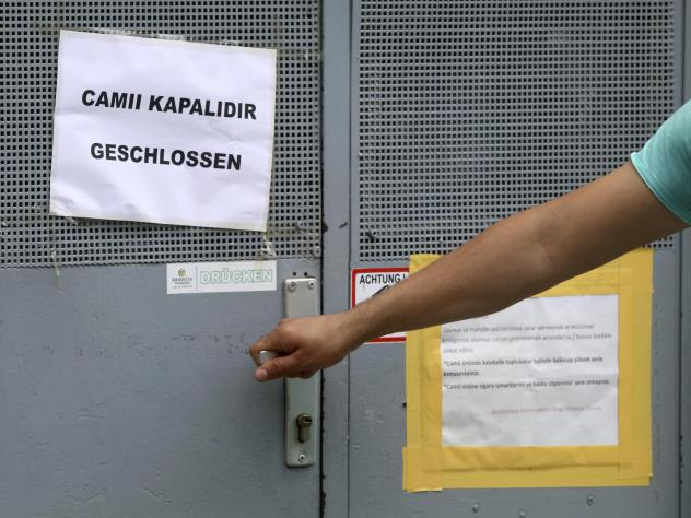 A person tries to open the door of a closed mosque in Vienna. The Austrian government said it's closing seven mosques as part of a crackdown on foreign financing of religious groups.