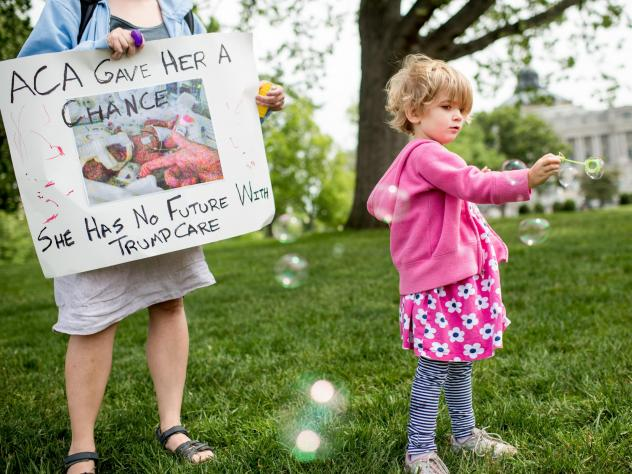Charlie Wood of Charlottesville, Va., plays with bubbles during a May 4, 2017, rally near the Capitol to oppose proposed changes to the Affordable Care Act. Charlie was born a few months prematurely, and her mother, Rebecca (left), fears changes to the h