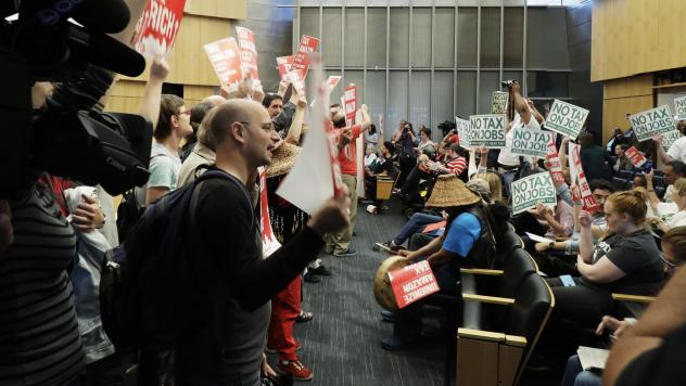 Supporters and opponents of a tax face off at Seattle City Hall on Tuesday.