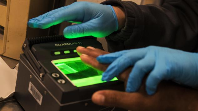 Immigration and Customs Enforcement agents take fingerprints while processing apprehended immigration fugitives inside the ICE staging facility in Los Angeles on April 18, 2017. Earlier this year ICE agents searching for an undocumented farmworker stoppe
