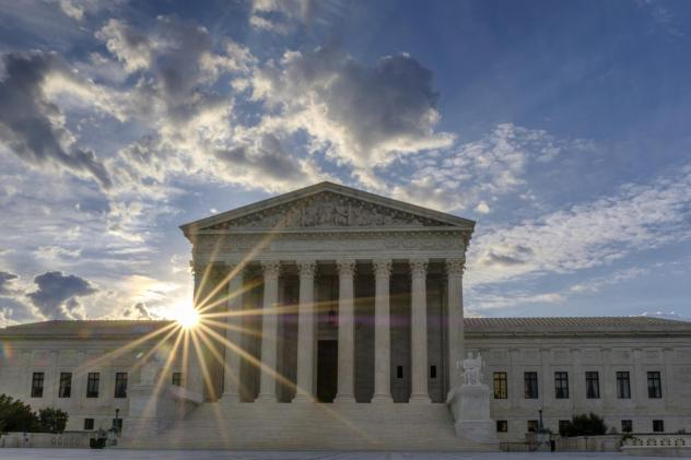 The sun flares in the camera lens as it rises behind the U.S. Supreme Court building in Washington.