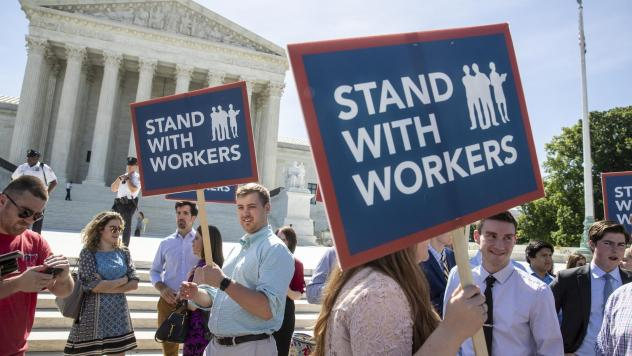 People gather Monday at the Supreme Court in Washington, D.C., awaiting a decision in an Illinois union dues case, <em>Janus v. AFSCME</em>.