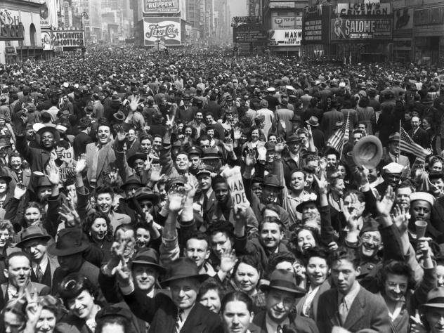 "An enormous New York crowd celebrates VE Day at the end of WWII. Aaron Copland was inspired to write his ""Fanfare for the Common Man"" by a wartime speech rallying Americans against imperialism."