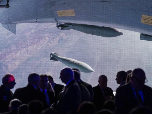 Participants at a global security conference in Moscow in April gather near a big screen showing a Russian warplane unloading its weapons over a target in Syria. Russia became involved in the Syrian civil war in 2015 in support of its ally President Bash