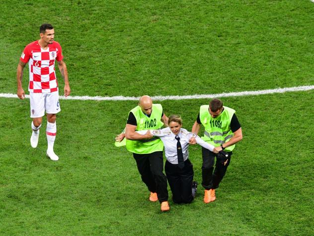 A member of the Russian protest-art group Pussy Riot is escorted by stewards during the Russia 2018 World Cup final football match between France and Croatia.