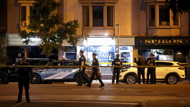 Police officers walk the scene in the Greektown neighborhood of Toronto Sunday night. Police say a gunman opened fire on 14 people in a restaurant. Three people are dead including the gunman, police reported.