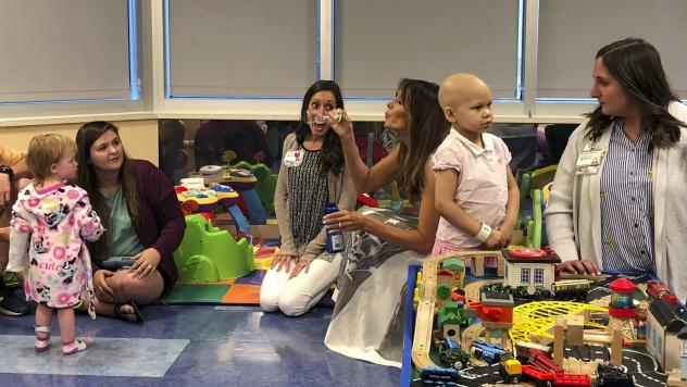 """Melania Trump blows bubbles in a playroom with children during a visit to Monroe Carell Jr. Children's Hospital in Nashville, Tenn., on Tuesday. The first lady was promoting her """"Be Best"""" campaign to help children."""