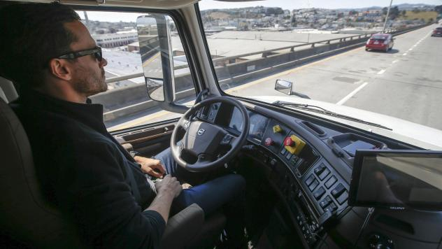 Two years after Uber paid $680 million to buy the self-driving truck startup Otto, the company is folding that effort. In this photo from 2016, an Otto engineer sits behind the steering wheel of a self-driving, big-rig truck during a demonstration in San