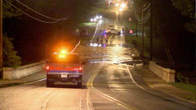 A screenshot from a video posted by the City of Lynchburg shows water flowing over Lakeside Drive, which runs atop the College Lake Dam in the Virginia city.