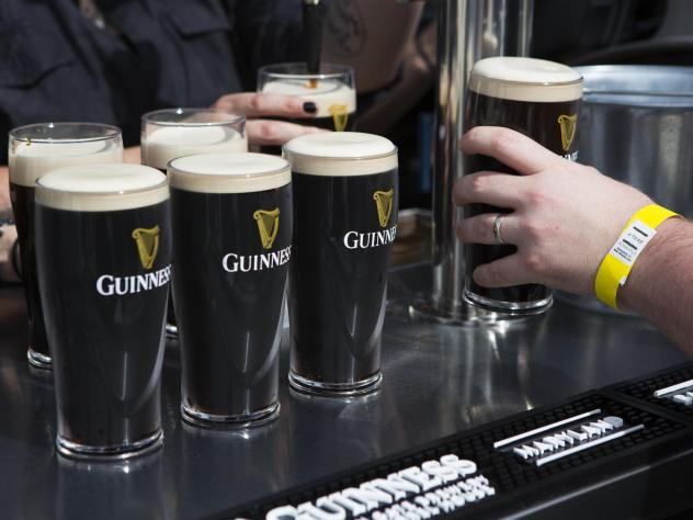"""Gene Nobel, 81, and David Johnson, 91, sit outside the brewery. The Guinness """"experience"""" includes a large lawn that's shaped like an imperial pint glass. It's big enough for around 4,000 people to hang out and listen to music."""