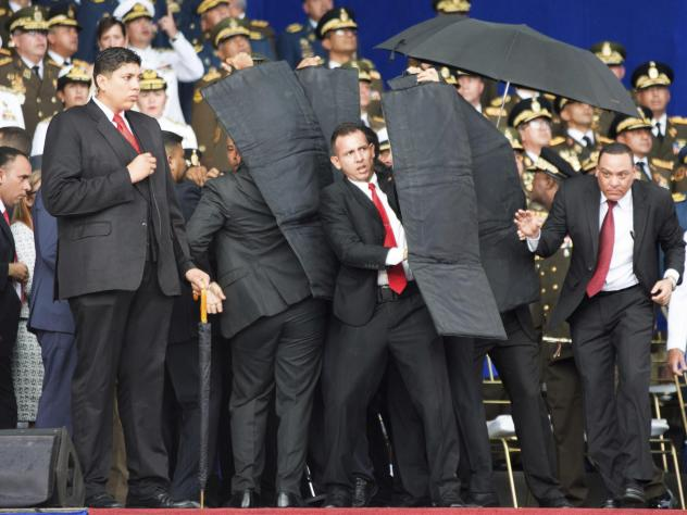 Security personnel surround Venezuela's President Nicolas Maduro after explosives-laden drones exploded near the podium where he was speaking in Caracas on Saturday. Maduro was unhurt.