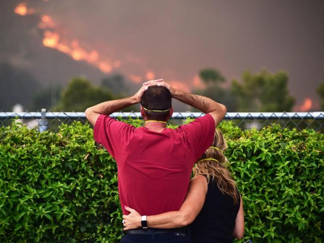 A firefighter looks on as the Holy Fire consumes a hillside Thursday in Temescal Valley in Corona, Calif.