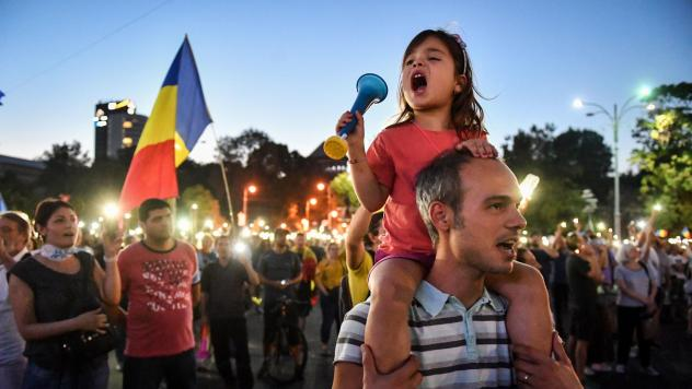 People wave Romanian national flags during a demonstration against the government on Saturday, during the second day of protests.