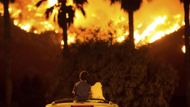 King Bass sits and watches the Holy Fire burn from on top of his parents' car as his sister, Princess, rests her head on his shoulder last week in Lake Elsinore, Calif. More than a thousand firefighters battled to keep a raging Southern California forest