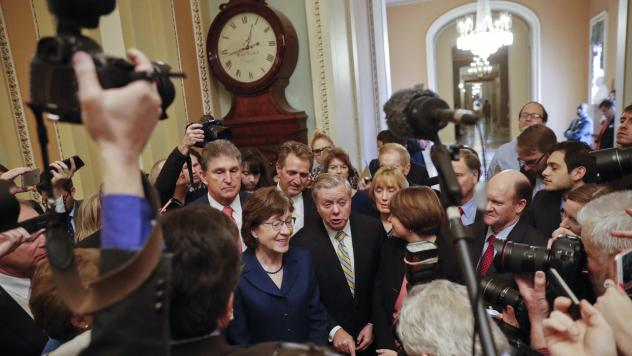Sen. Lindsey Graham, R-S.C., speaks to members of the media outside the Senate Chamber in Washington, Jan. 22, 2018, after reaching a bipartisan agreement to advance a bill ending the government shutdown. With Graham are (L-R) Sen. Joe Manchin, D-W.Va.,