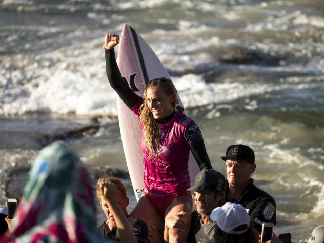 U.S. surfer Lakey Peterson is carried up the beach after claiming victory in a World Surf League event in Australia in March. The league says it will start paying the same prize money to men and women.