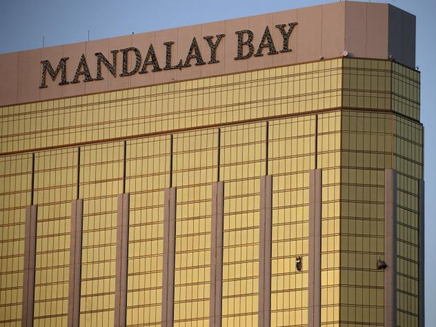 On Oct. 2, 2017, drapes billow out of broken windows at the Mandalay Bay resort on the Las Vegas Strip, following a deadly shooting at a music festival. On Tuesday, the company that owns the hotel offered to make a $500 charitable donation for victims wh
