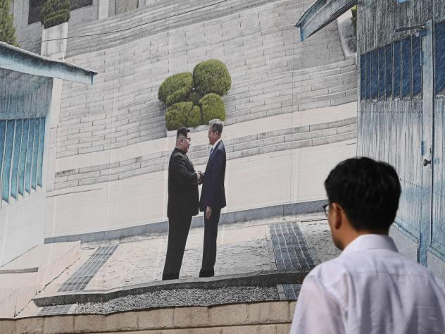 A man walks past a giant banner showing a picture of the summit handshake between South Korean President Moon Jae-in and North Korean leader Kim Jong Un, at Seoul City Hall on Sept, 13. Moon will fly to North Korea's capital on Sept. 18 for a third summi