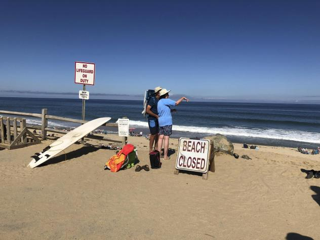 Two people look out at the water after a shark attack at Newcomb Hollow Beach in Wellfleet, Mass., on Sept. 15.