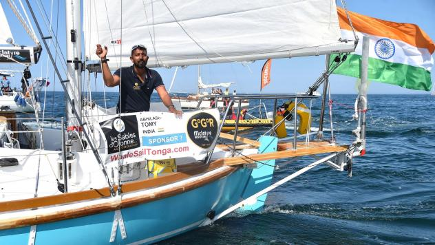 """India's Abhilash Tomy gestures on his boat Thuriya as he sets off from Les Sables d'Olonne Harbour on July 1 at the start of the solo around-the-world """"Golden Globe Race"""" ocean race in which sailors compete without high technology aides such as GPS or co"""