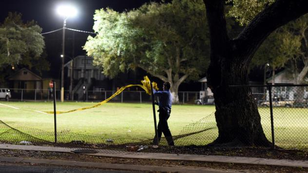 A police officer removes crime scene tape after a shooting at a playground in New Orleans, in 2015.